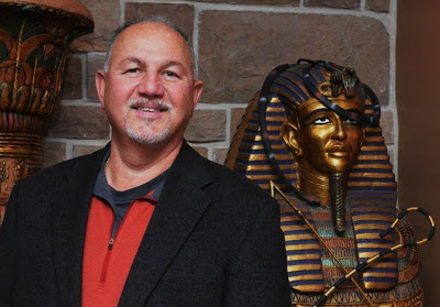Photo of John Ventre next to a statue of Queen Nefertiti, or perhaps it's a variation on King Tut.